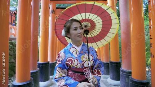 Wall mural Asian women in traditional japanese kimonos walking at Fushimi Inari Shrine in Kyoto, Japan. 4K