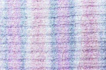 Knitted texture of white, pink, lilac and blue colors