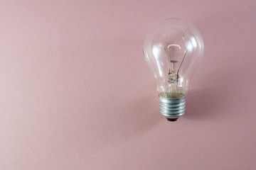Glowing light bulb on pink background useful to demonstrate various concepts