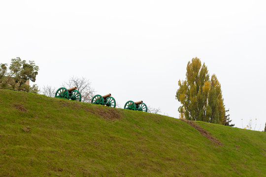 Old cannons, built in a redoubt on a hill. Old cannons stand on high ground, at a strategic height. Three old cannons stand on a hill against a white sky with trees.