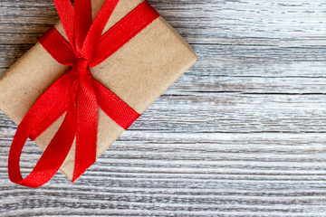 A gift box, beautifully wrapped with kraft paper and red ribbon and large bow on wooden background with copy space