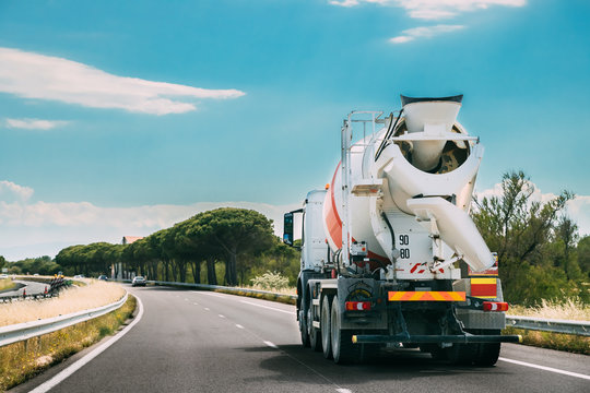 Concrete Transport Truck In-transit Mixer Unit In Motion On Coun