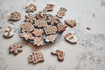 Fresh and tasty Christmas gingerbread cookies placed on white rusty table. Different shapes. Santa claus, snowflake, tree, gift, snowman.