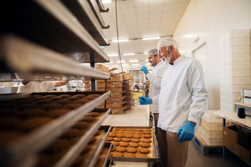 Workers packing cookies in boxes while standing in food factory.
