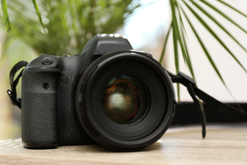 Professional camera on table against blurred background. Photographer's equipment