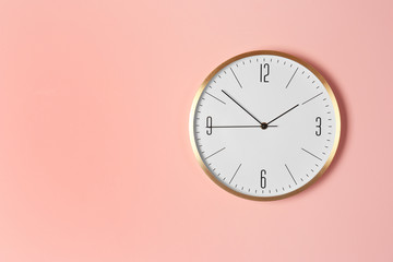 Stylish analog clock hanging on color wall. Space for text