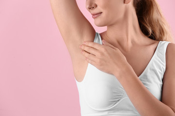 Young woman showing armpit on color background, space for text. Using deodorant