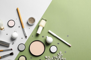 Flat lay composition with makeup products and Christmas decor on color background. Space for text