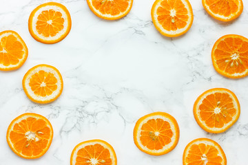 Fresh orange slices on white marble background top view