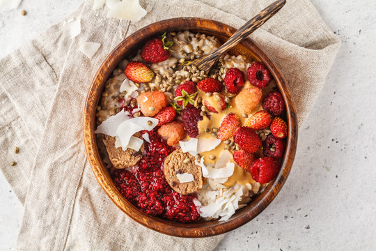 Trendy vegan bowl of oatmeal porridge with berries, raw vegan balls and peanut butter.