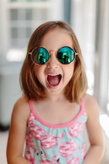 Cute young girl with sunglasses making a surprised face