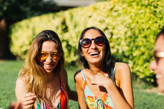 Hispanic friends at swimming pool, enjoying summer