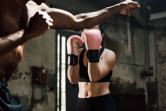 Strong brunette woman boxing indoors with her coach.