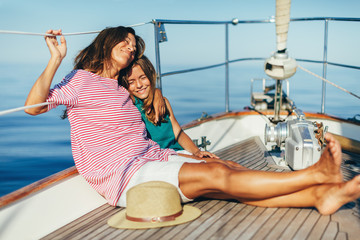 Mother and daughter enjoying a sunny day on a sailboat.