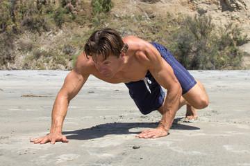 Man doing bear crawl workout on beach