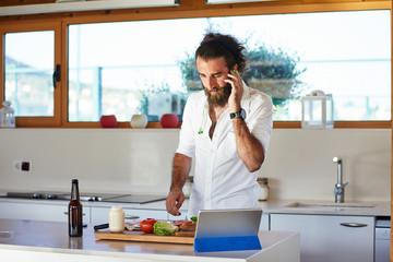 Man putting on headphones in kitchen