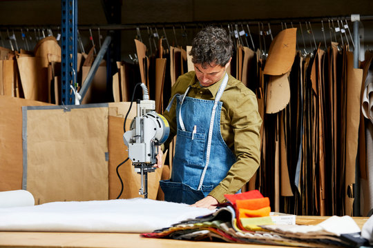 Worker Using Fabric Cutting Machine In Sofa Workshop