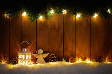 Christmas background with branches, lantern and decoration on dark wooden board