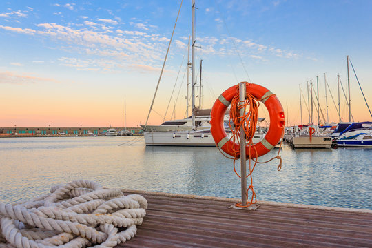 the quay of a marina at  the sunset /a mooring rope with a lifebelt  on  the quay of a marina at  the sunset