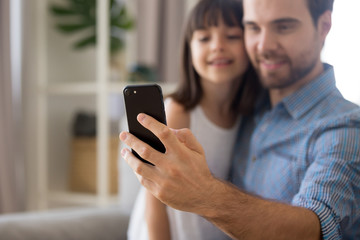 Smiling father and little cute preschool daughter looking at smartphone screen taking selfie portrait photography sitting on couch, focus on male hand close up. Family have fun use technology concept
