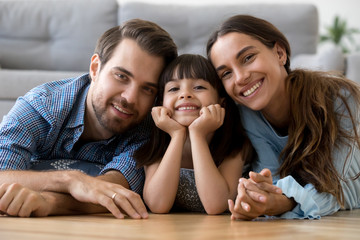 Multi-ethnic diverse family lying at cushions on warm floor in living room at modern home smiling looking at camera. Young mother adorable daughter handsome father feels happy spend free time together