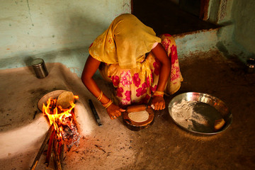 Traditional way of making food cooking on open fire in a rural village,near Kajiraho,India