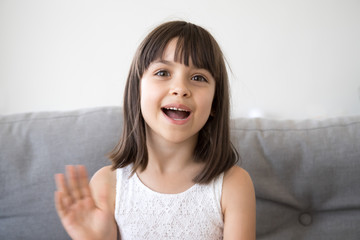 Small girl sitting on couch alone at home. Head shot portrait little adorable daughter waving hand looking at camera smile saying hello or goodbye. First acquaintance and online communication concept
