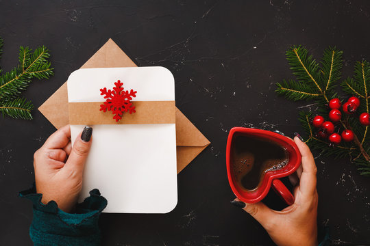 Christmas background with female hand  and a coffee cup decorated with evergreen plants, red berry holly and gift on rustic dark surface, top view