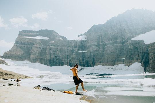 Shirtless man splashing water near lake against mountain