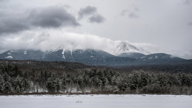 Beautiful winter landscape, mountain in the clouds and snow covered trees. Katahdin, Maine, USA