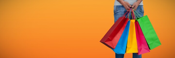 Composite image of low section of man carrying colorful shopping