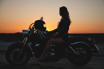 Woman biker at sunset, a trip on a motorcycle, a journey through freedom
