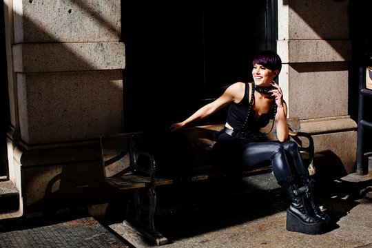 Portrait of a beautiful young woman in a black leather outfit smiling and sitting on a bench