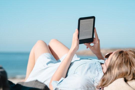 Frau liest mit E-Book Reader am Strand