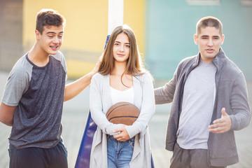 Teen boys and girl with basketball ball