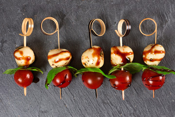 Spoed Fotobehang Voorgerecht Caprese salad skewers with mozzarella, basil, tomatoes and balsamic glaze. Appetizers against a dark stone background.