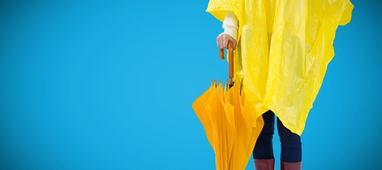 Composite image of woman in yellow raincoat holding an umbrella
