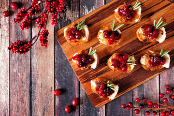 Spoed Fotobehang Voorgerecht Holiday crostini appetizers with cranberries, brie and caramelized onions. Above view on a wooden platter
