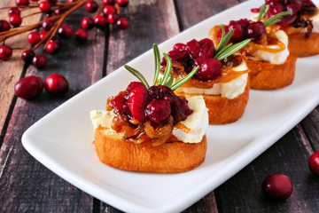 Crostini appetizers with cranberries, brie and caramelized onions. Close up on a serving plate against a wood background.