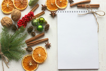 Christmas card, white paper notebook background surrounded by Christmas balls, fir branches, cinnamon sticks, spices, dried orange, wooden deer . Copy space.
