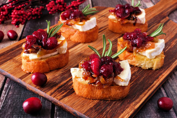 Crostini appetizers with cranberries, brie and caramelized onions. Close up table scene on a wood platter.