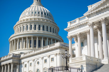 Bright blue sky view of the US Capitol Building under midday sun in Washington DC, USA
