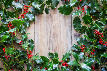 Seasonal background of weathered wood framed by sprigs of green Christmas holly with red berries