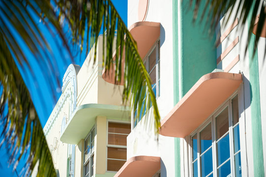 Bright scenic view of colorful pastel details of Art Deco architecture behind palm fronds in South Beach, Miami, Florida
