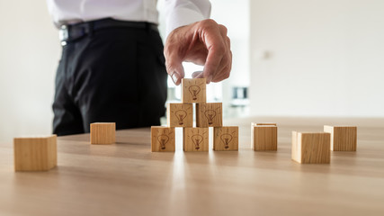 Business vision concept -businessman arranging wooden cubes