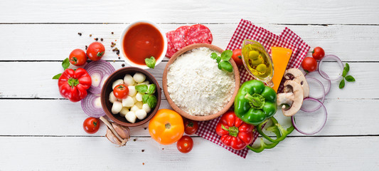 Ingredients for pizza. Mushrooms, sausages, tomatoes, vegetables. Top view. On a white wooden background. Free copy space.
