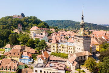 Green hills, spires and red tiled roofs of Walled old town of Sighisoara (Sighishoara), Mures, Transylvania, Romania. The Clock Tower of Sighisoara. Aerial view.