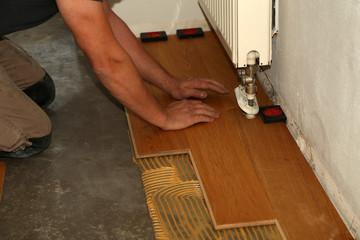 Obraz Worker laying parquet flooring. Worker installing wooden laminate flooring. - fototapety do salonu