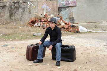 Hombre sentado sobre maleta negra