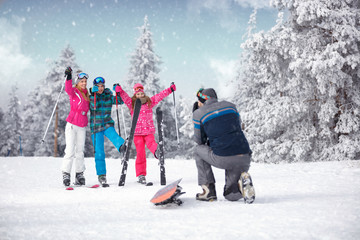 taking photographing of family on winter vacation in snow mountains
